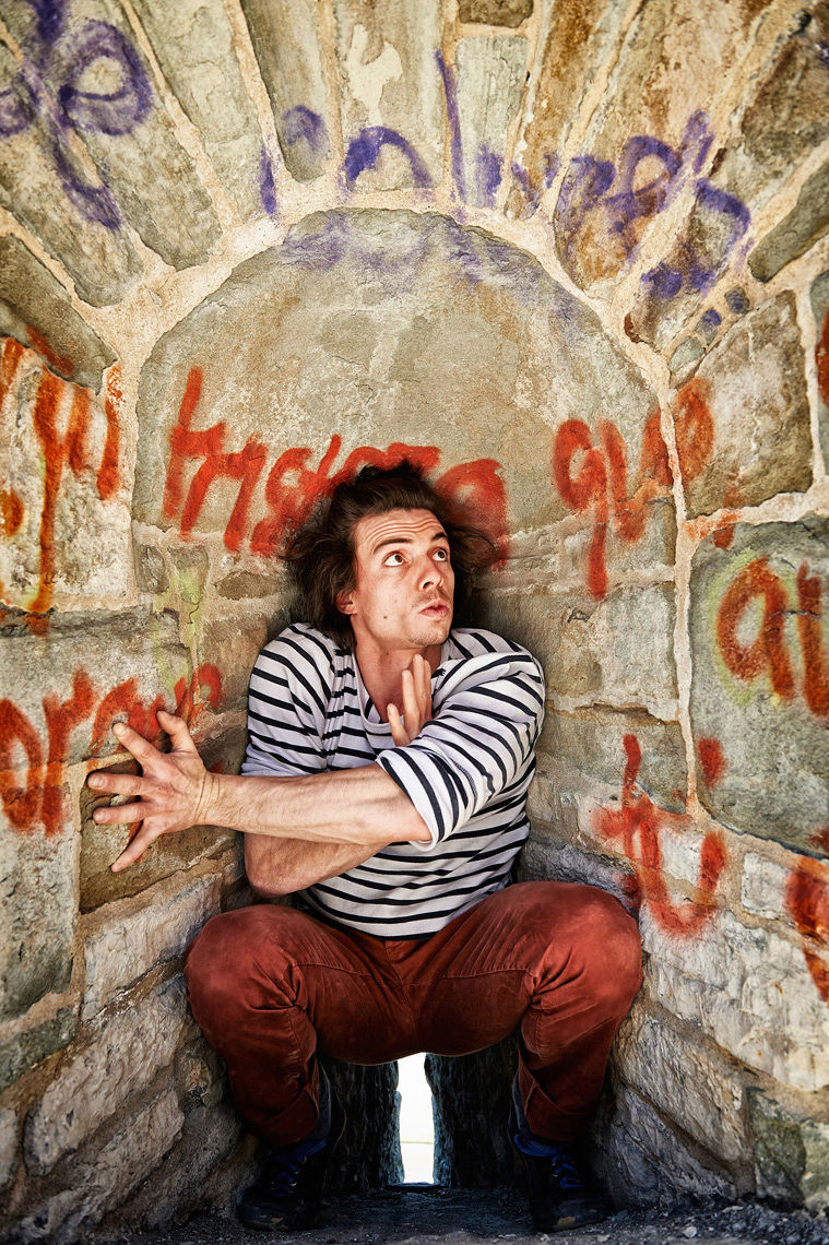 Young French man crouched in a small space with graffitti