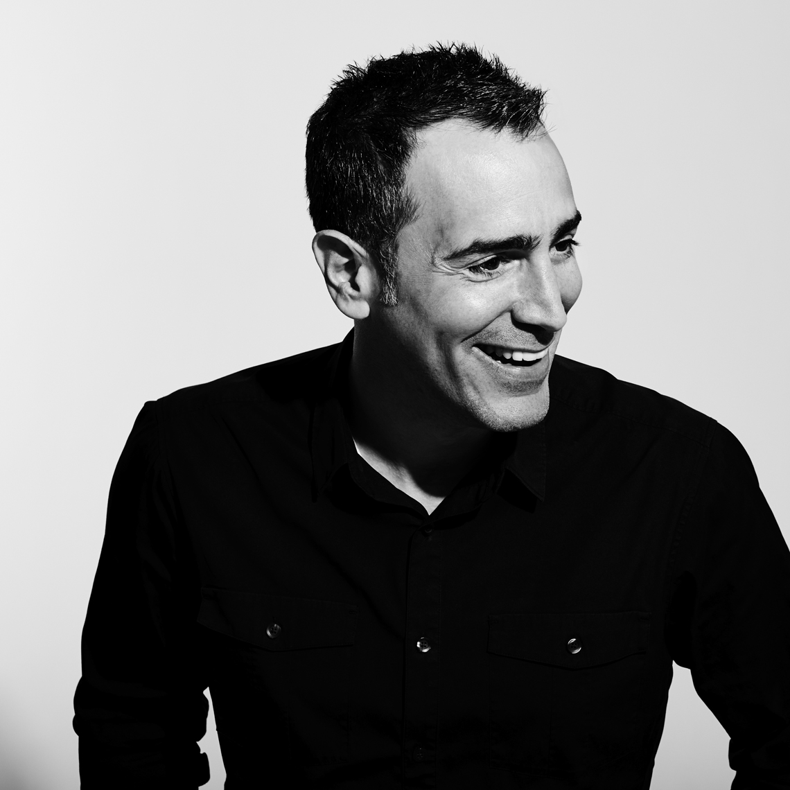 black and white portrait of Joe laughing off camera